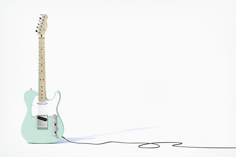 Green guitar balancing on white background