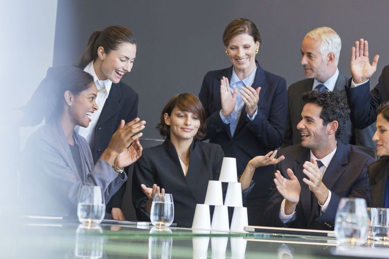 group of business professionals applauding a leader who accomplished a difficult task