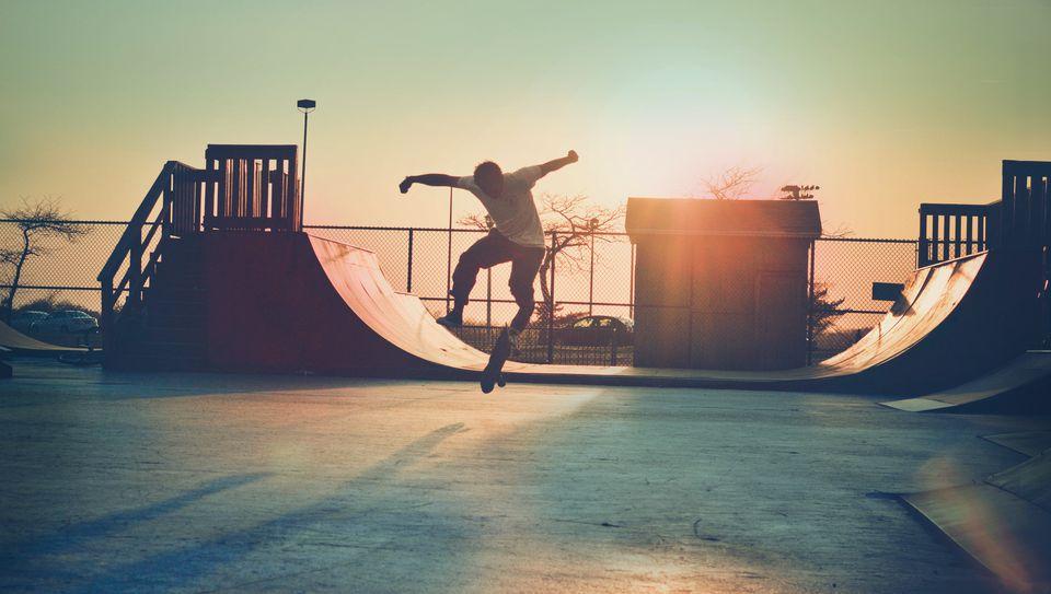 Skateboarder jumping at the skatepark at dusk.