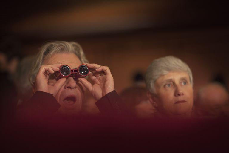 Man looking through binoculars for good financial advice.
