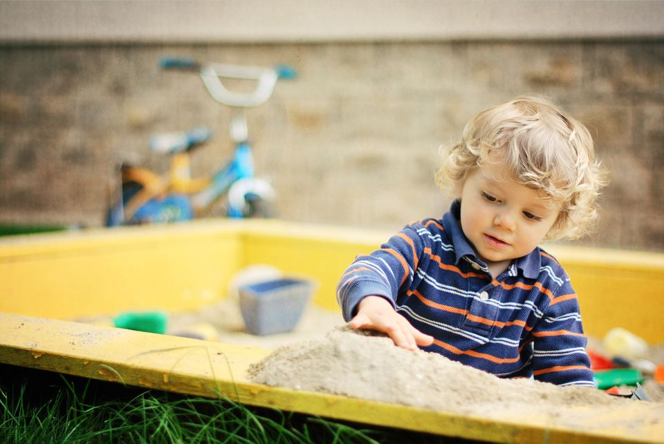 Child playing in sandbox.