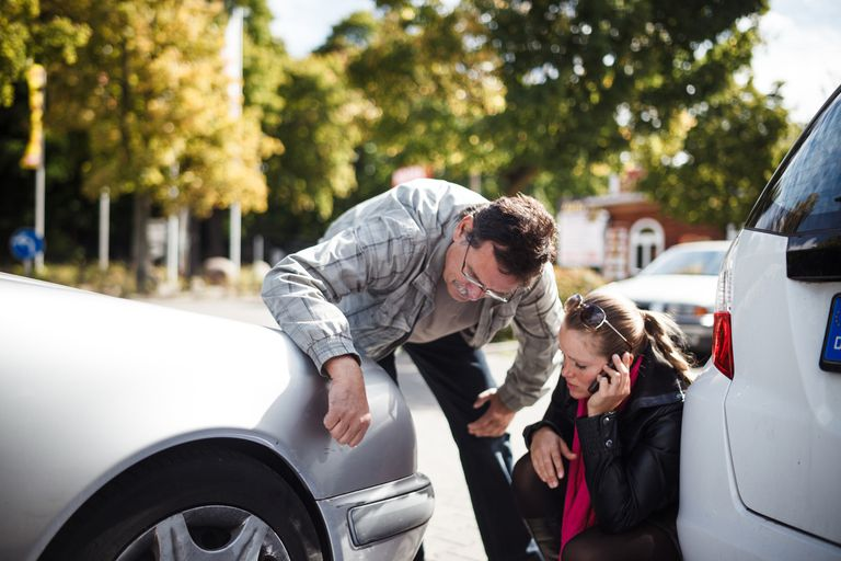 Man and women examining car after accident.