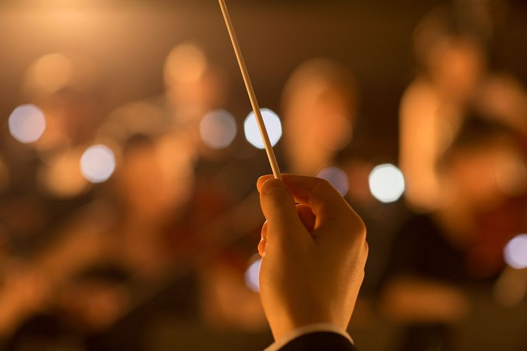 Close up of orchestra conductor holding baton.