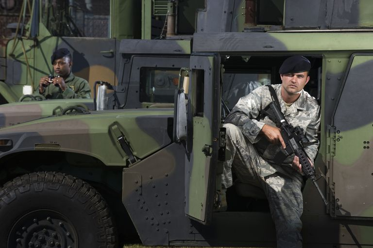 Military police officers secure tactical vehicles on base.