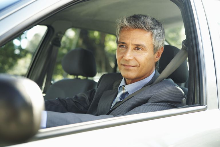 Man in a suit sitting in the driver's seat of a car