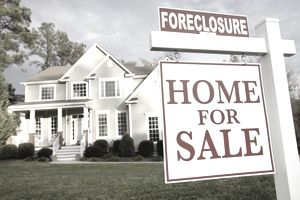 Home with foreclosure sign in front yard