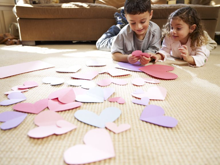 Brother (8-9) and sister (3-4) playing with paper heart templates, lying on floor