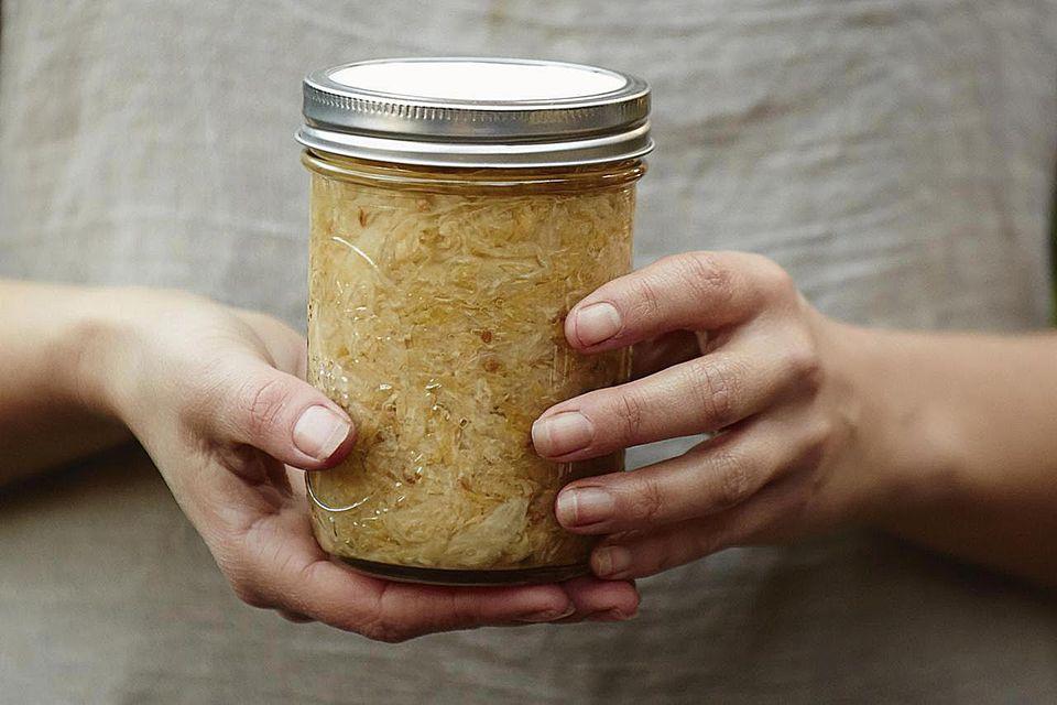 Woman holding jar of fermented sauerkraut