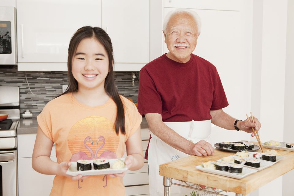 Girl making sushi with her grandfather.