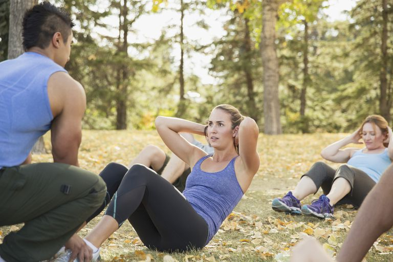 women with personal trainer doing outdoor boot camp workout