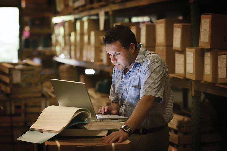 Man using laptop in warehouse, side view