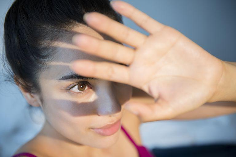 Hispanic woman shielding herself from light