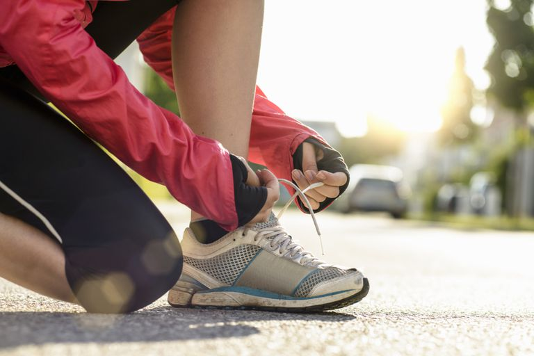 Female runner tying shoe lace in a urban area