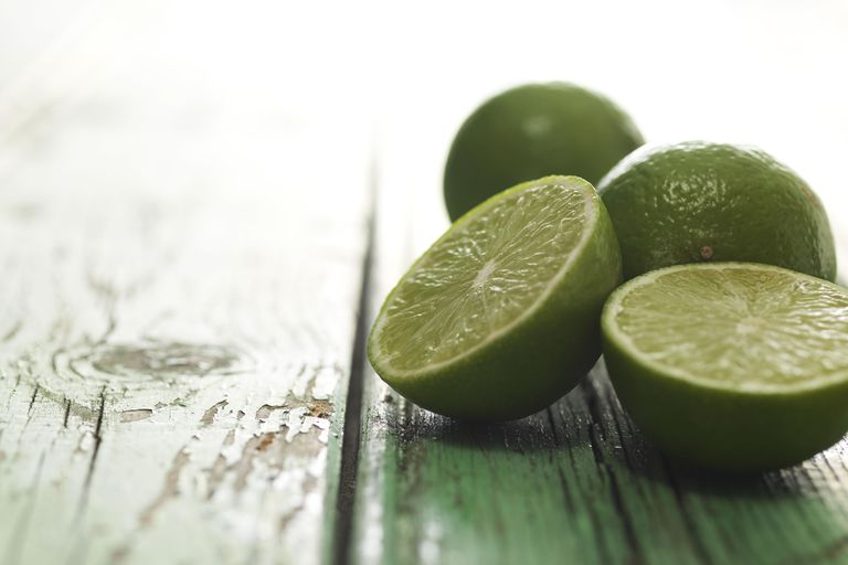 sliced limes on wooden table