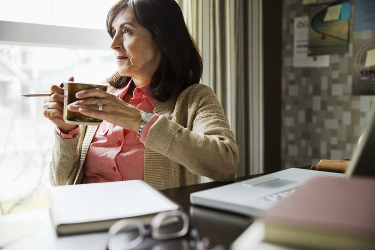 Pensive woman drinking coffee in home office