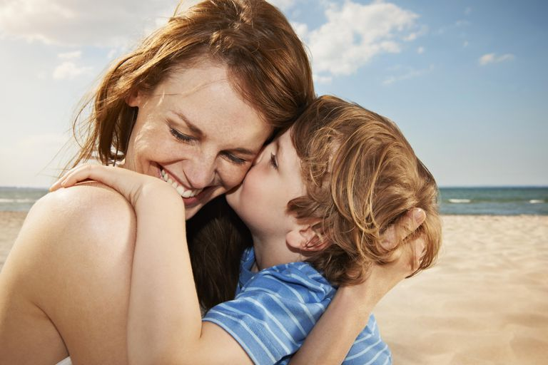 Boy (4-5 years) kissing mother, smiling, close up