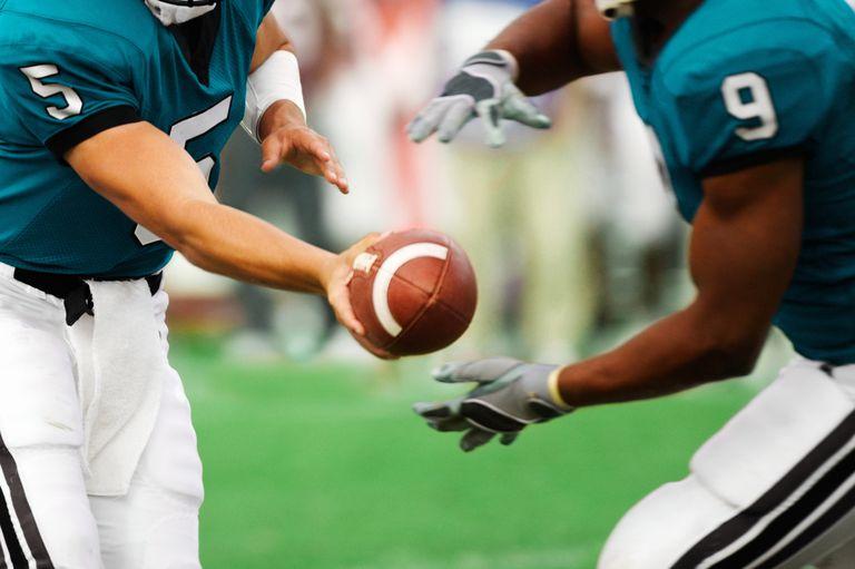 Quarterback handing off football to running back