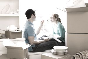 couple eating takeout meal at their new house next to boxes