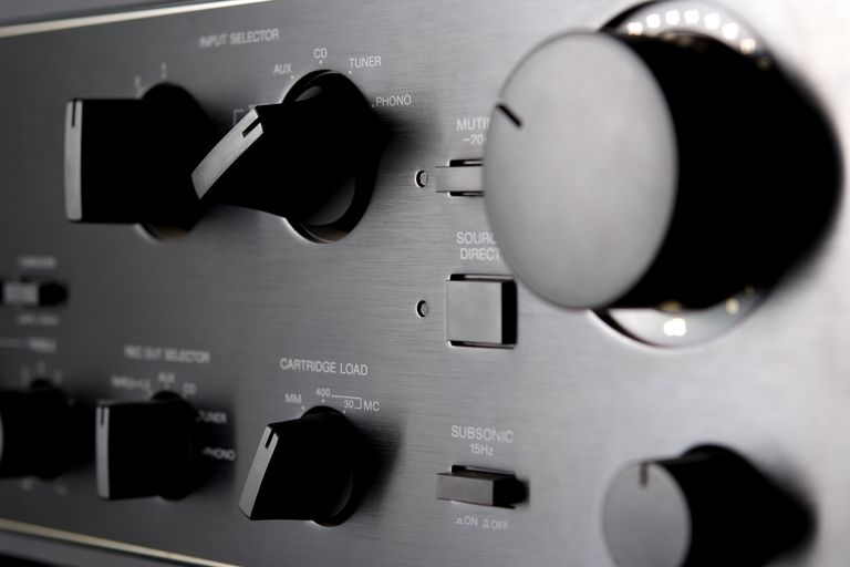 The front panel of a stereo receiver showing knobs for volume and input