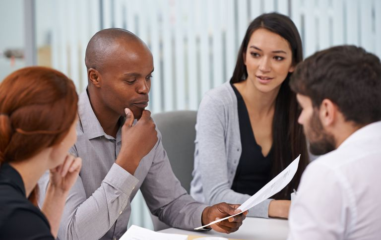 Business people in a conference room with a candidate assessing his cultural fit with their interview questions.