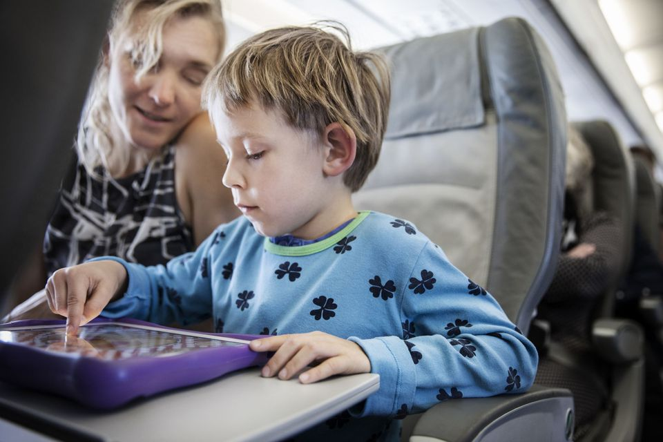 A picture of a child playing a game on an airplane