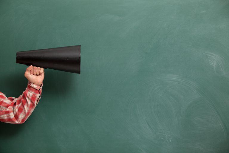 man holding megaphone against chalk board