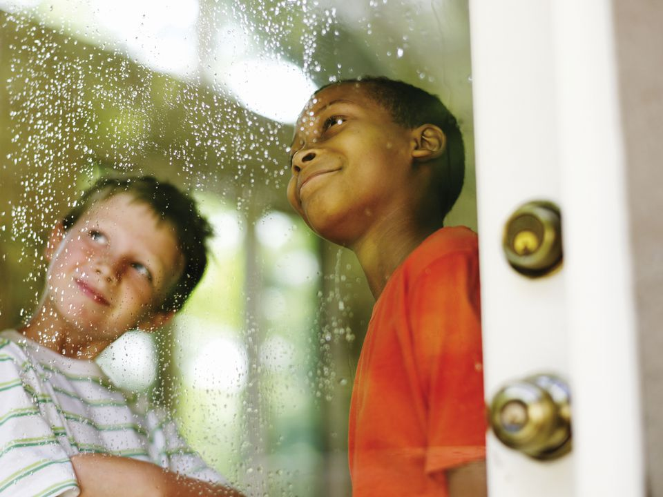 two boys looking out window on rainy day