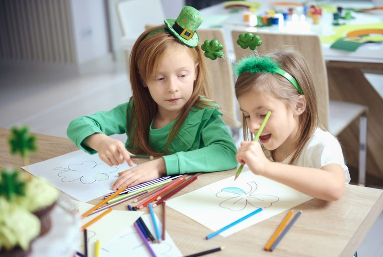 Cheerful siblings coloring different illustrations