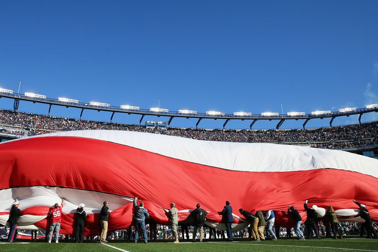 Giant US Flag being waved before football game.
