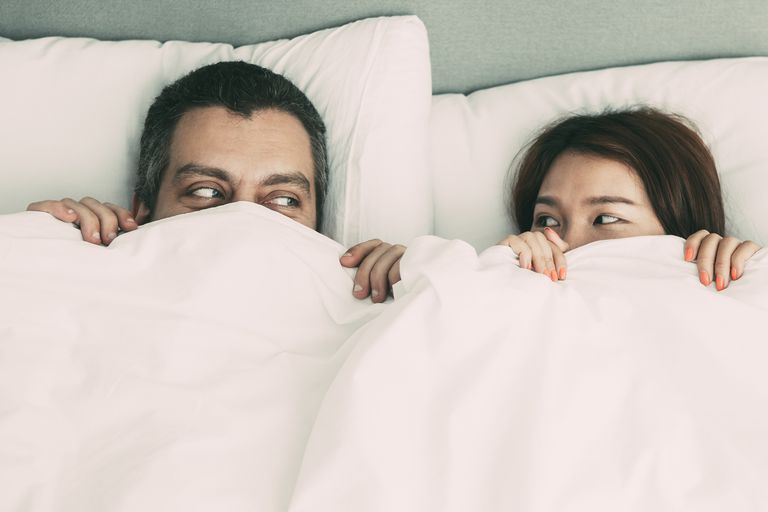 Playful Couple Hiding Behind Blanket in Bed