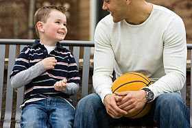 A young child sits on a bench with his mentor.