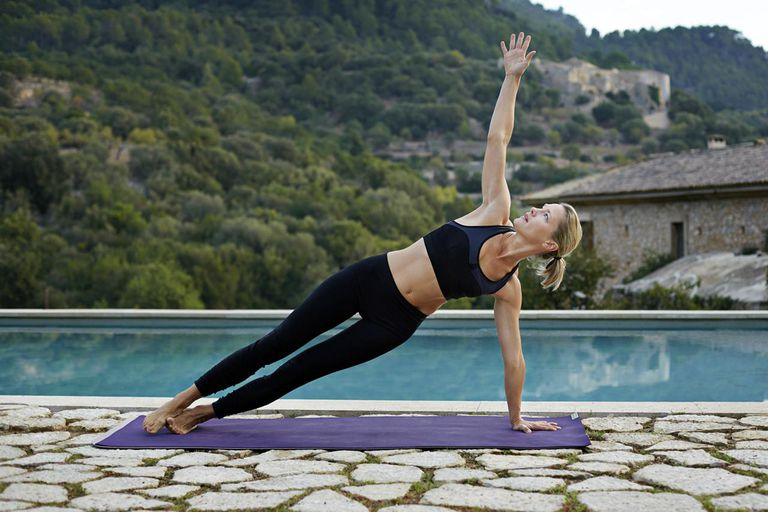 Beautiful woman practicing yoga by pool area in the mountains