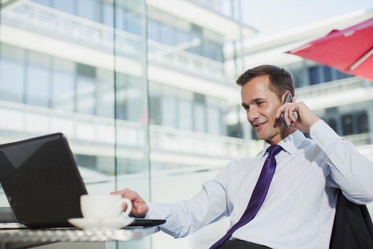 Businessman using laptop and talking on cell phone in office