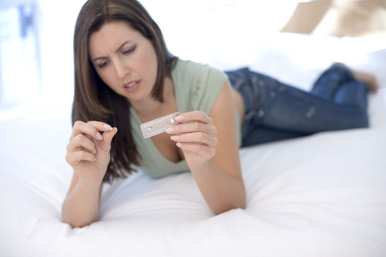 woman considering birth control pills