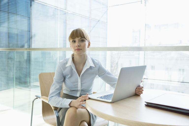 Businesswoman with laptop sitting at table in office