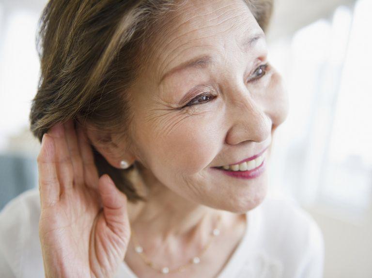 Japanese woman listening with hand near ear