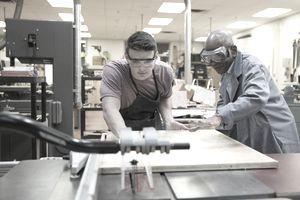 High school teacher guiding student at woodcutting machine
