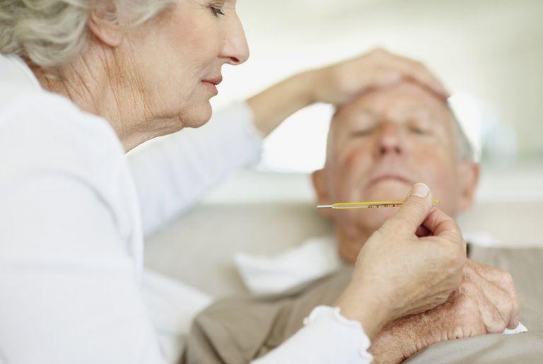 senior woman taking sick husband's temperature