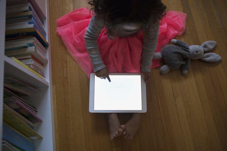 Overhead girl using digital tablet on floor