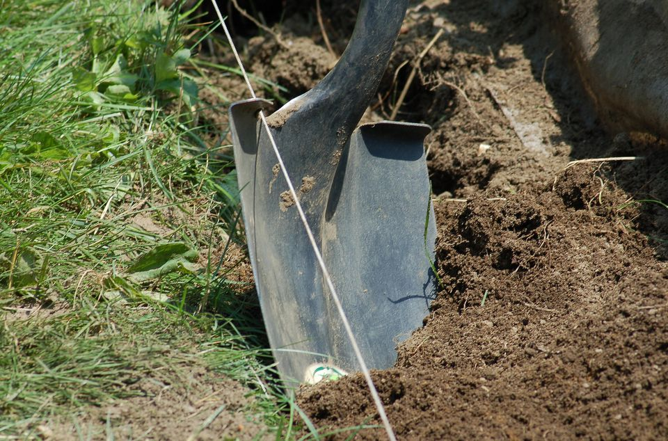 Image: shovel plunged into the earth.