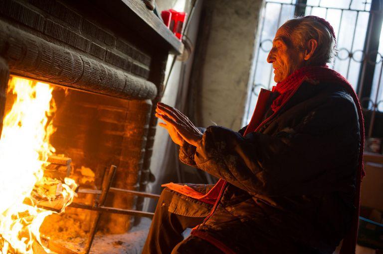 Older man warming himself by fireplace