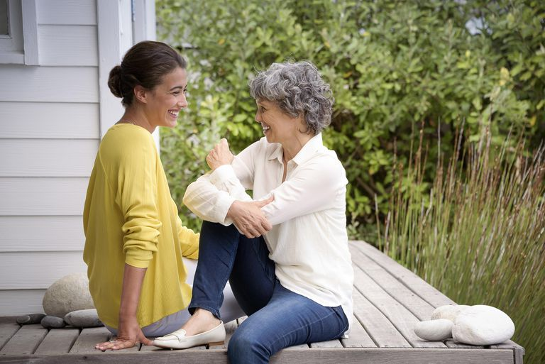 Happy mother talking with her adult daughter on porch