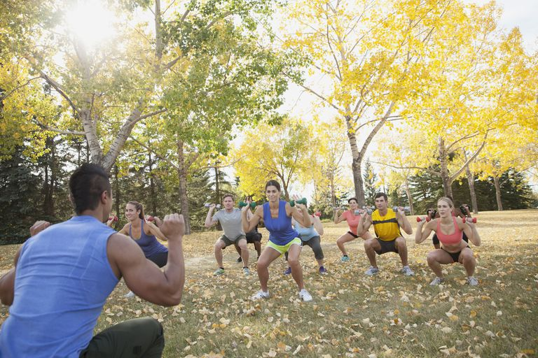 Man leading fitness class in a weight squat outside