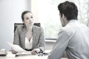 Manager speaking with employee across a desk