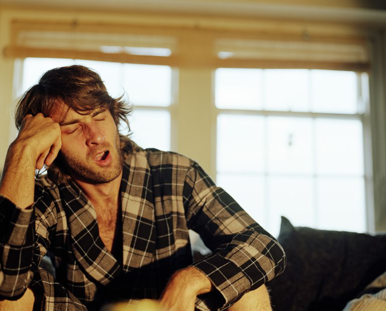 Man in bathrobe yawning, head resting on hand, eyes closed