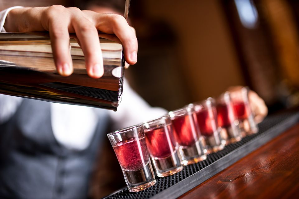 Bartender pouring pink shots into shot glass