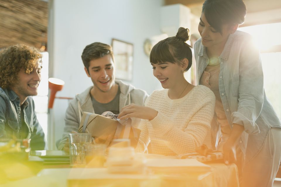 Young couples celebrating birthday opening gift at table