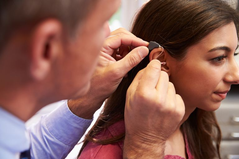 Doctor fitting hearing aid in girl's ear