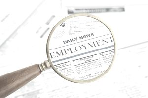 Close-up of job listing seen through magnifying glass