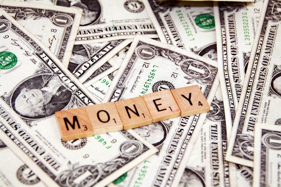 """US currency with the word """"money"""" spelled out with Scrabble letters"""